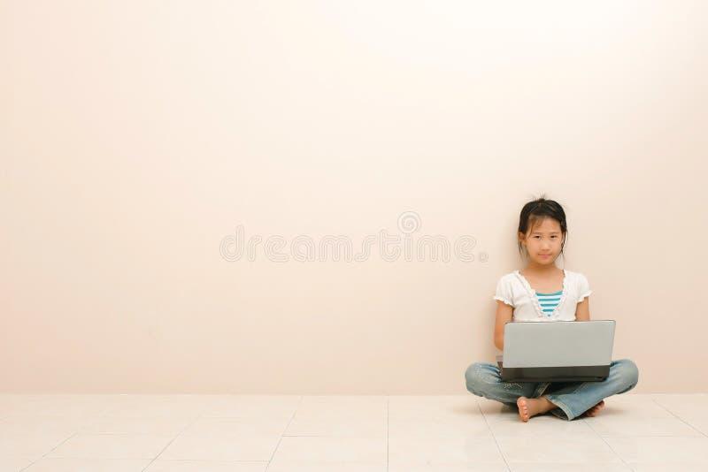 Aziatisch meisje gebruikend laptop en bekijkend camera tegen roze achtergrond royalty-vrije stock foto's