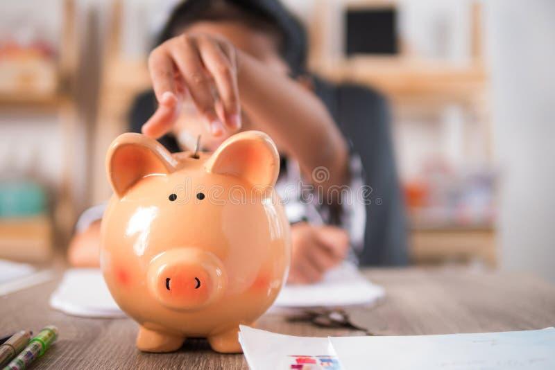 Aziatisch meisje in het aanbrengen van muntstuk aan de ondiepe diepte van het spaarvarken stock foto