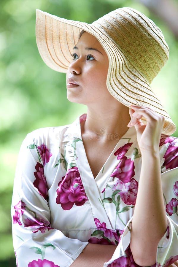 Aziatisch meisje met de brede hoed van het randstro in het park stock fotografie