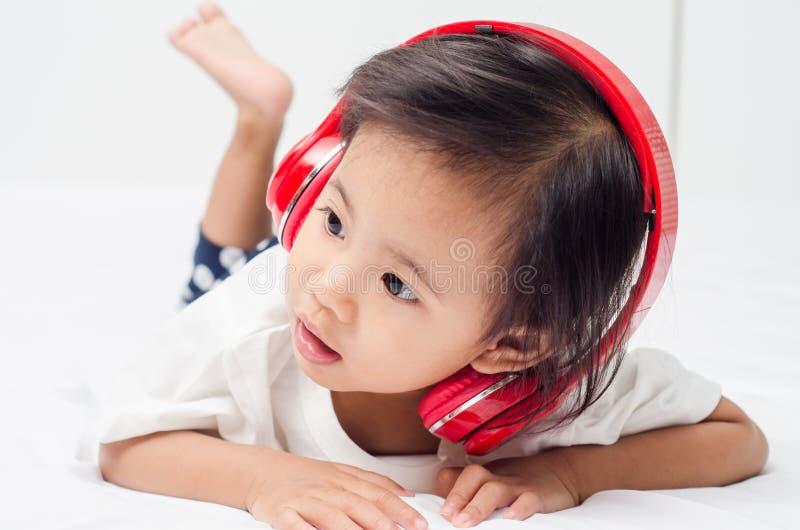 Aziatisch meisje met hoofdtelefoons die op het bed thuis liggen stock afbeelding