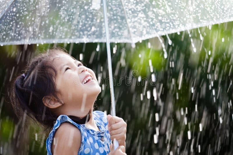 Aziatisch meisje met paraplu in regen stock foto