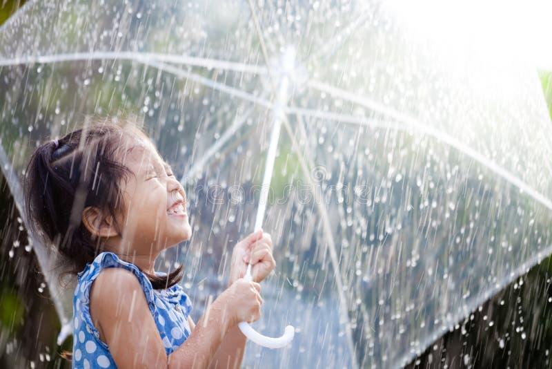 Aziatisch meisje met paraplu in regen stock fotografie