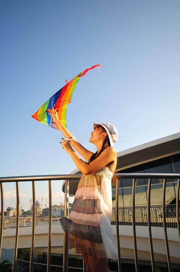 Aziatisch Meisje met vlieger onder de zon stock fotografie