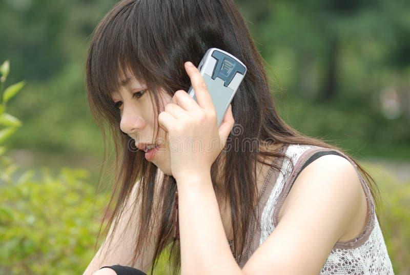 Aziatisch meisje op celtelefoon royalty-vrije stock afbeeldingen
