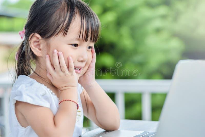 Aziatisch meisje in openlucht met lachebekje die laptop in de tuin thuis met behulp van het concept van de familieactiviteit royalty-vrije stock afbeeldingen