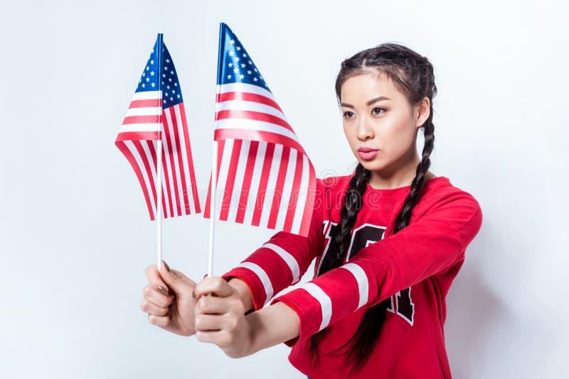 Aziatisch meisje in patriottische Amerikaanse vlaggen houden en uitrusting die weg eruit zien royalty-vrije stock afbeeldingen