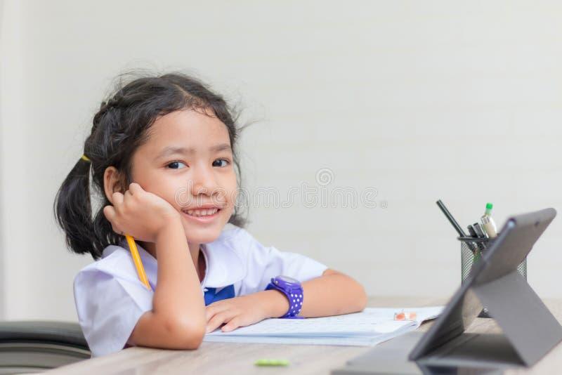 Aziatisch meisje in student eenvormig het doen thuiswerk en het gebruiken van tablet op de houten ondiepe diepte van de lijst uit stock foto's