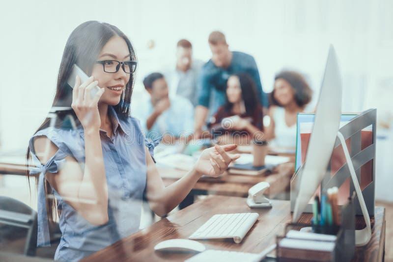 Aziatisch Meisje talking telefoon work Groot bureau royalty-vrije stock foto's