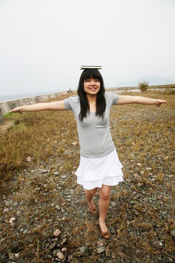 Aziatisch meisjes in evenwicht brengend boek op hoofd royalty-vrije stock foto