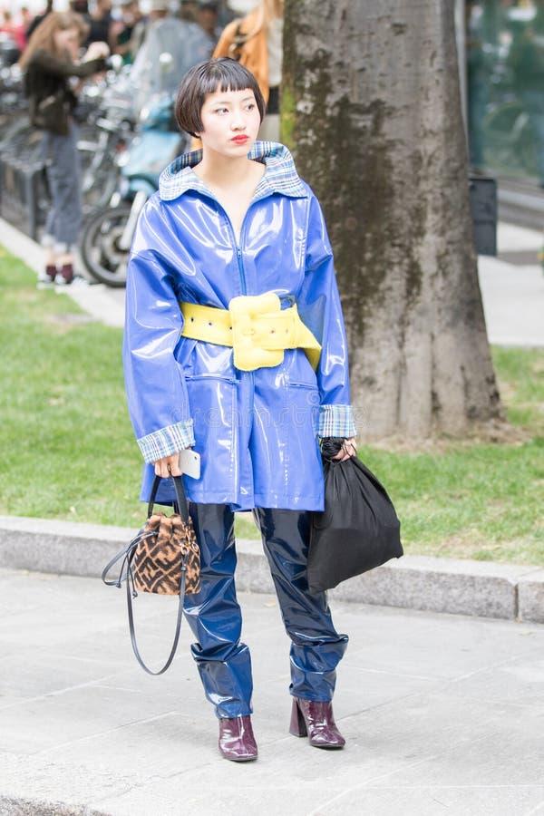 Aziatisch model met een blauw, poetsende rubberen broek met een elektroblauwe jas in glanzend rubber met een opvallende gele riem royalty-vrije stock fotografie