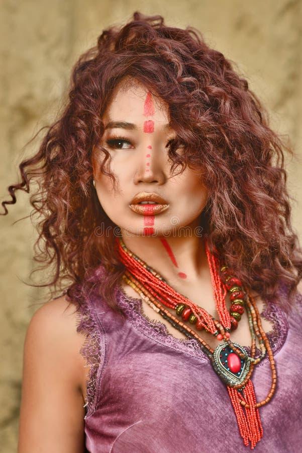 Aziatisch model met samenstelling op gezicht in feulettekleding tegen hooibergachtergrond stock afbeeldingen