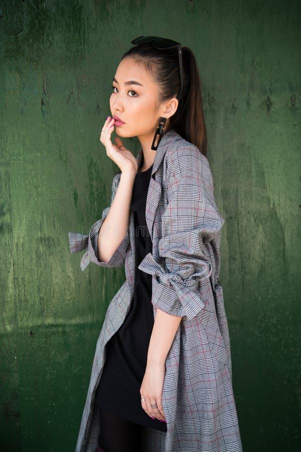 Aziatisch modelmeisje die dragend toevallige modieuze uitrusting dichtbij houten groene muur stellen stock foto's