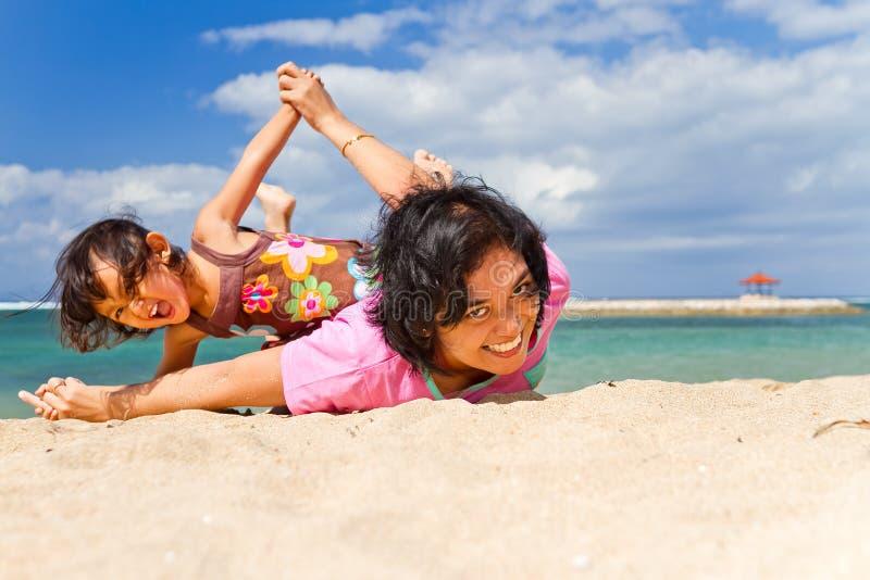 Aziatisch moeder en kindpretspel bij het strand stock afbeelding