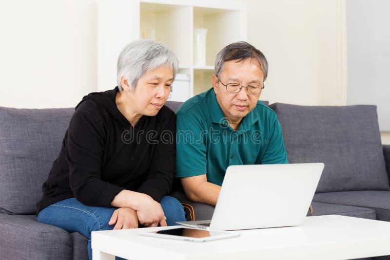 Aziatisch oud paar dat laptop met behulp van royalty-vrije stock foto's