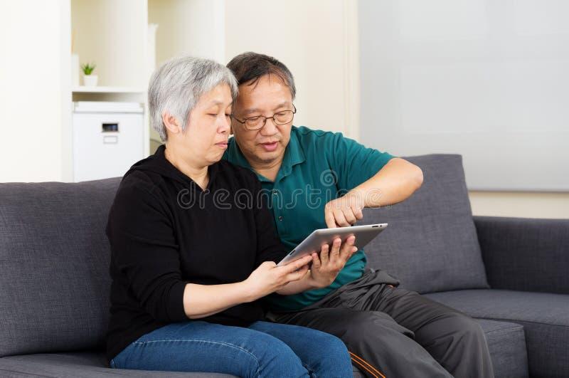 Aziatisch oud paar die tablet samen gebruiken stock foto's