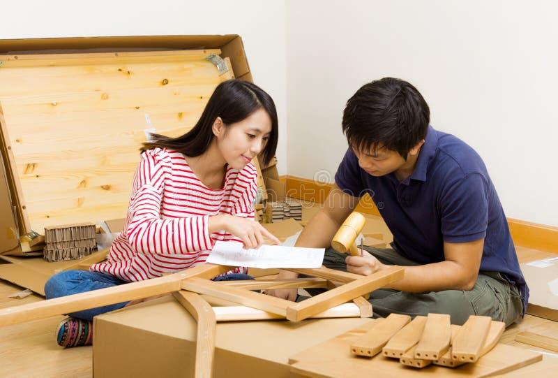 Aziatisch paar dat nieuw meubilair assembleert royalty-vrije stock foto