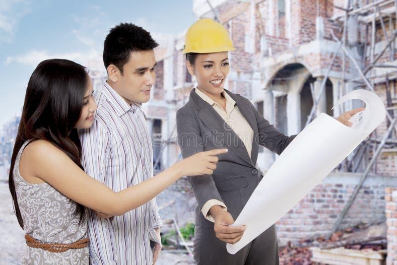 Aziatisch paar die aan immobiliënontwikkelaar spreken royalty-vrije stock foto