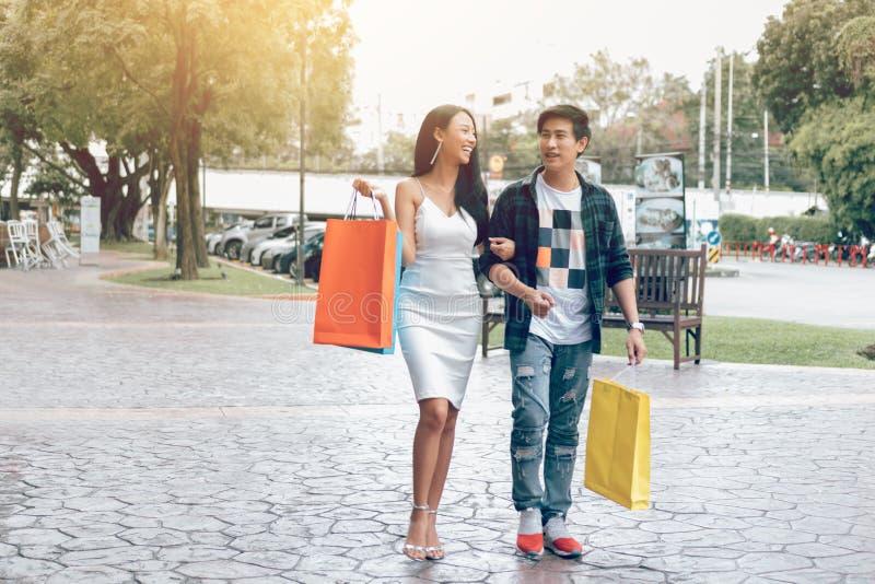 Aziatisch paar die bij straat lopen en het winkelen zakken houden royalty-vrije stock foto's