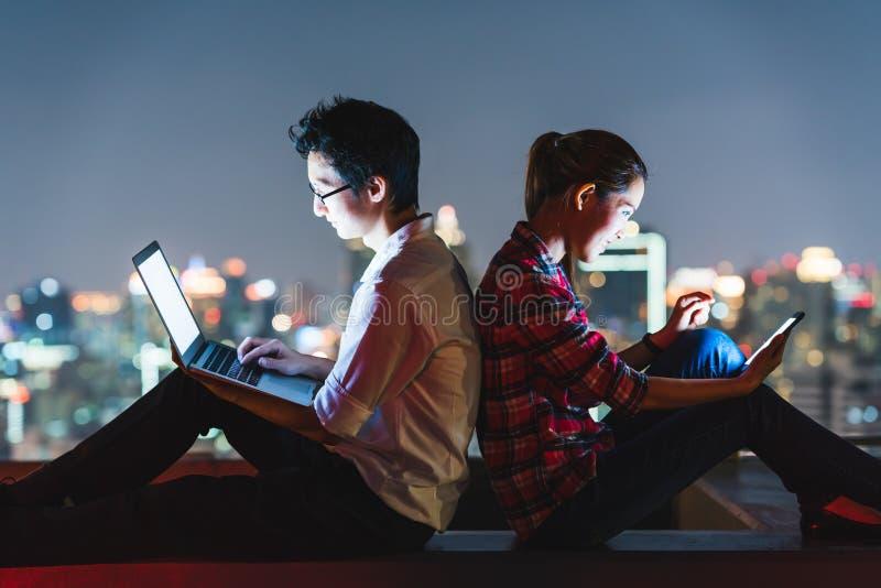 Aziatisch paar die laptop en smartphone gebruiken samen, helling op elkaar op dak bij nacht stock foto