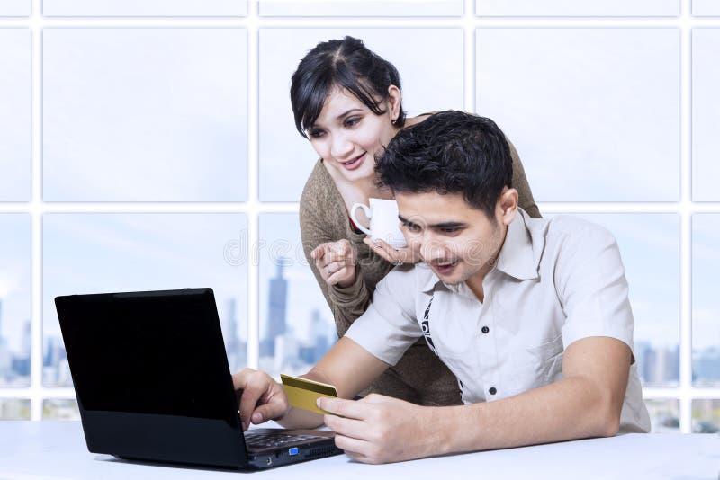Aziatisch paar die online in bureau betalen die creditcard gebruiken stock fotografie