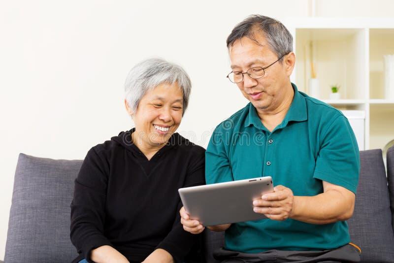 Aziatisch paar die tablet samen bekijken stock foto's