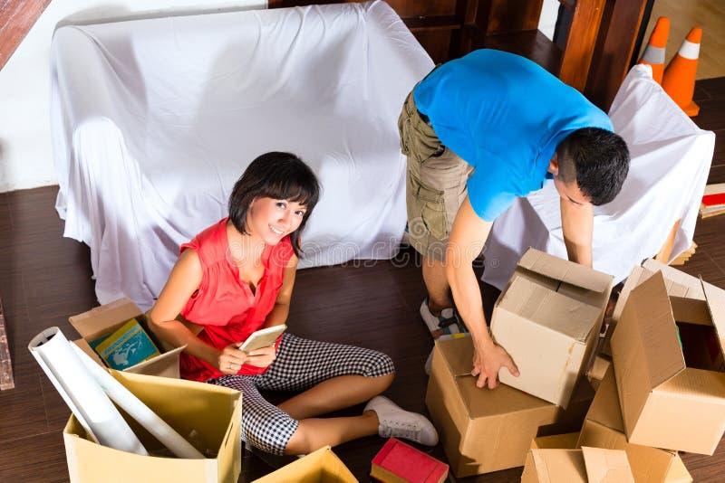 Aziatisch paar die zich in het nieuwe huis bewegen royalty-vrije stock afbeelding