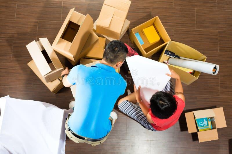Aziatisch paar die zich in het nieuwe huis bewegen stock fotografie
