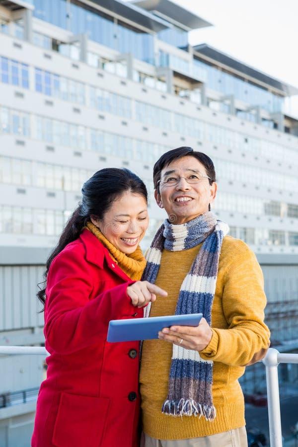 Aziatisch paar op balkon die tablet gebruiken stock foto's