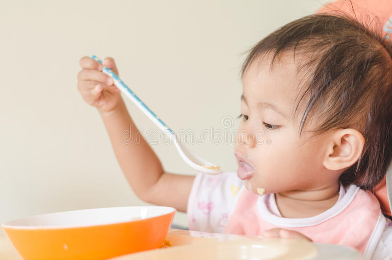 Aziatisch peutermeisje die graangewassen met melk op hoge stoel eten bij hom stock afbeeldingen