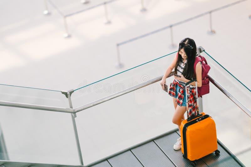 Aziatisch reizigersmeisje, student die smartphonevraag of praatje gebruiken bij luchthaven met bagage, rugzak Webcontrole binnen, royalty-vrije stock foto's