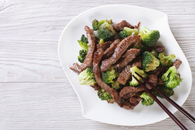 Aziatisch rundvlees met broccoli en eetstokjes horizontale hoogste mening stock foto's