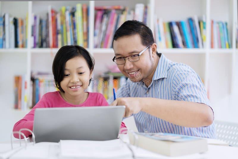 Aziatisch schoolmeisje die door haar leraar worden onderwezen royalty-vrije stock afbeeldingen