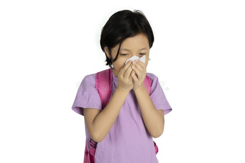 Aziatisch schoolmeisje die haar neus met een weefsel afvegen stock foto