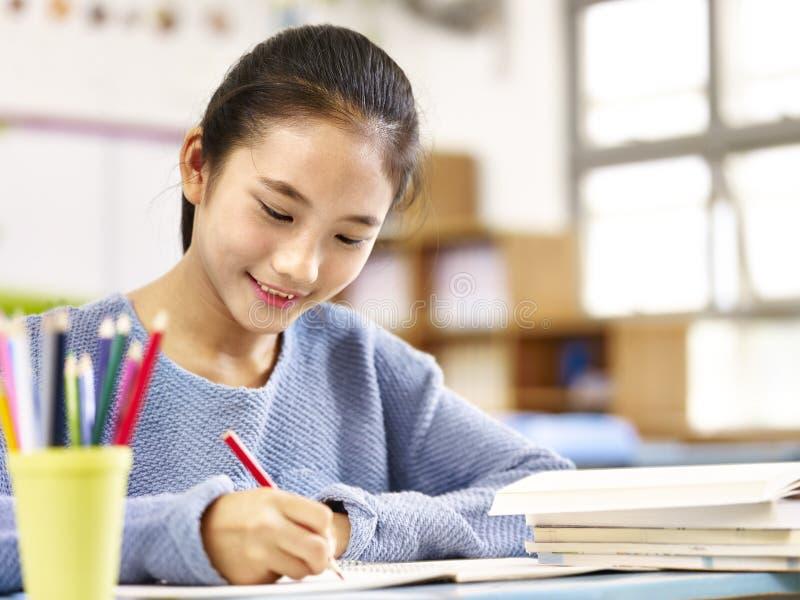 Aziatisch schoolmeisje die in klaslokaal bestuderen stock afbeelding