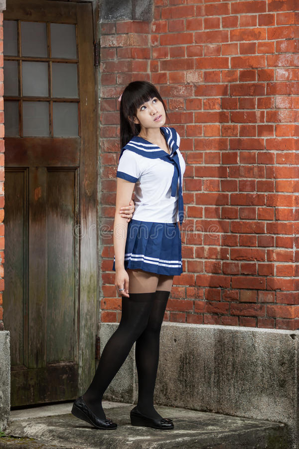 Aziatisch schoolmeisje die zich voor school bevinden royalty-vrije stock foto