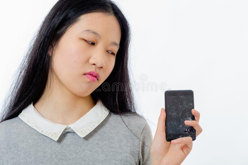 Aziatisch schoolmeisje met gebarsten cellphone stock afbeelding