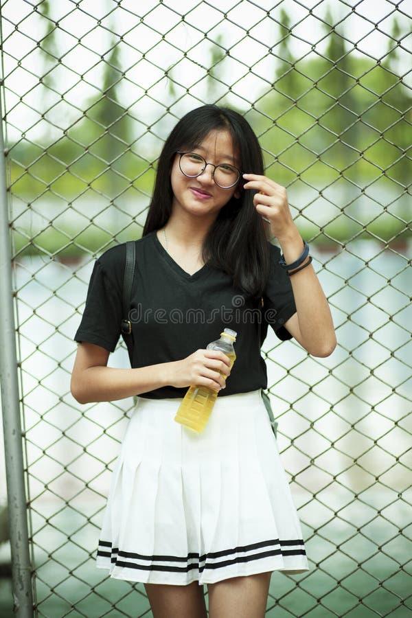 Aziatisch tiener het glimlachen gezicht die pastic fles in hand houden stock afbeelding