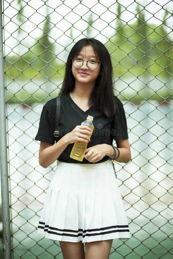 Aziatisch tiener het glimlachen gezicht die pastic fles in hand houden royalty-vrije stock afbeelding