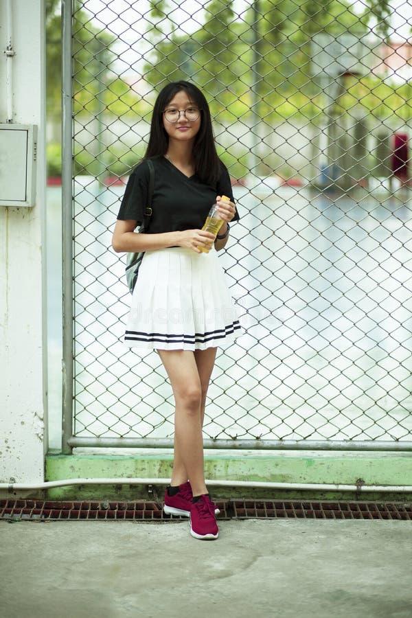 Aziatisch tiener het glimlachen gezicht die pastic fles in hand houden royalty-vrije stock fotografie