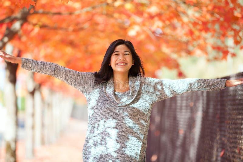 Aziatisch tienermeisje die onder de rode uitgestrekte wapens glimlachen van de esdoornboom royalty-vrije stock afbeeldingen
