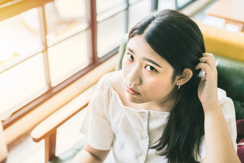 Aziatisch tienermeisje die vraag en krassend hoofd kijken stock foto