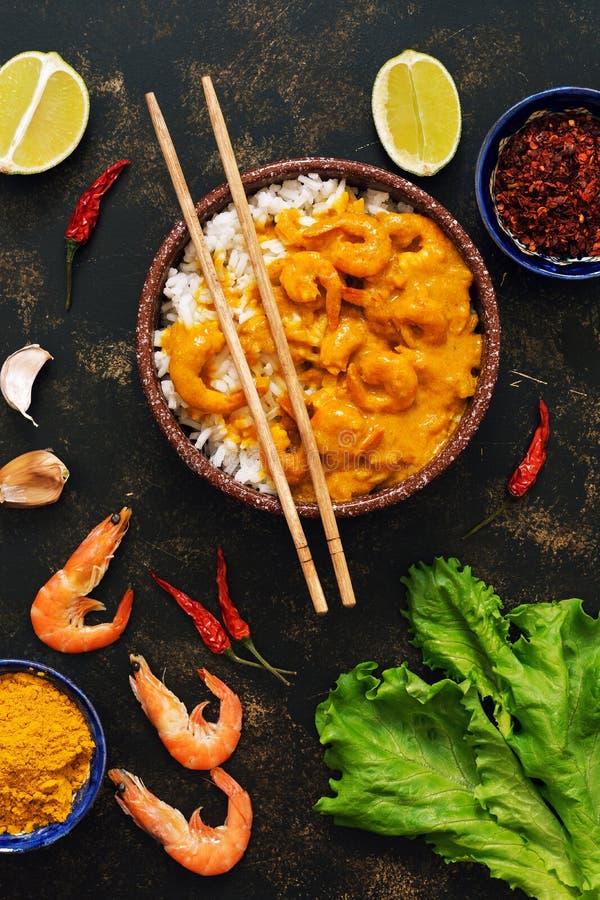 Aziatisch voedsel, garnalen in kerriesaus met rijst op een donkere achtergrond royalty-vrije stock afbeeldingen