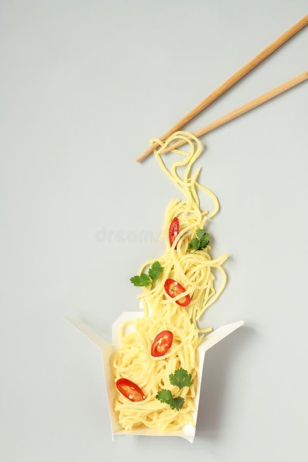 Aziatisch voedsel met eetstokjes De Aziatische einoedels met Spaanse peper en koriander halen document binnen vakje, hoogste meni royalty-vrije stock foto