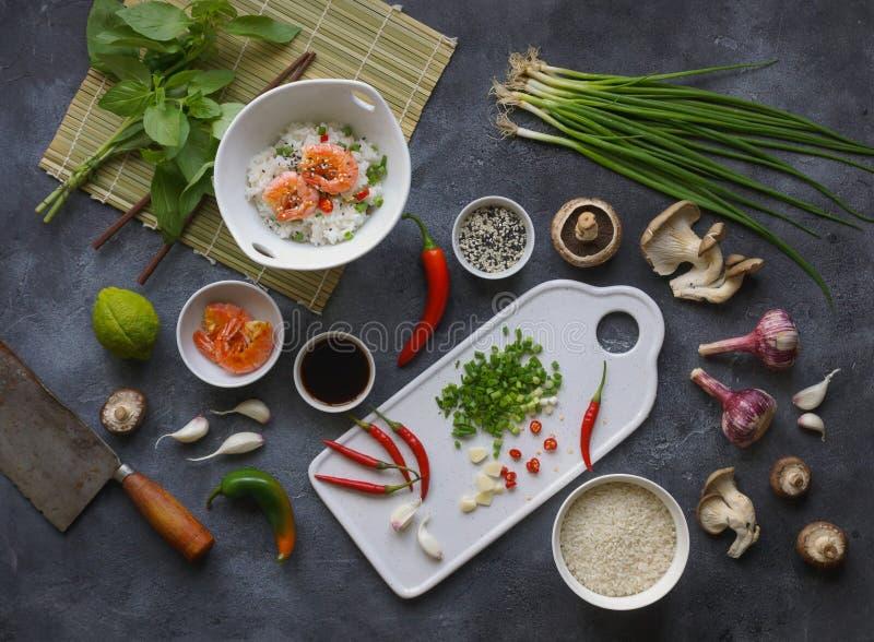Aziatisch voedsel op een donkere achtergrond, Wokrijst met garnalen en paddestoelen, tijdens voorbereiding stock foto's