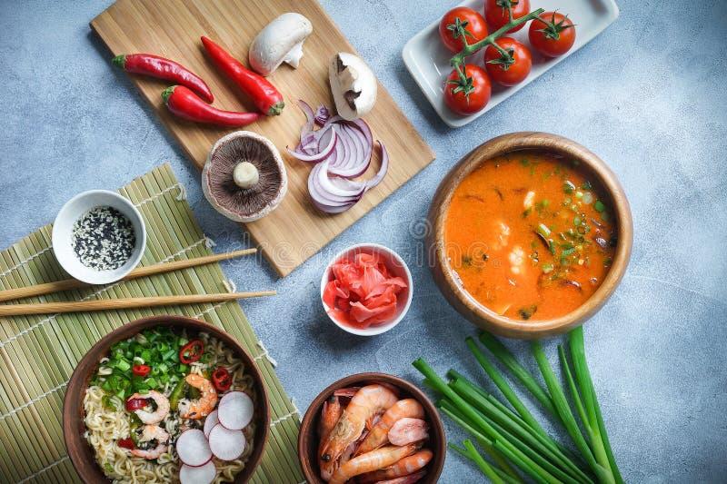 Aziatisch voedsel, Tom Yam en Ramen met garnalen, Thais voedsel in houten kom, Einoedels, Voorbereiding, Spaanse peperspeper, ui  stock fotografie