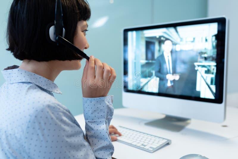 Aziatisch Vrouwelijk klantenservice uitvoerend makend videogesprek op computer bij bureau stock fotografie