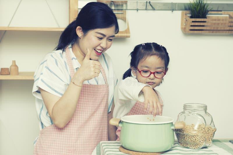 Aziatisch vrouwenmamma met daugther in keuken, meisjespel met pinda en mamma thrump omhoog met gelukkige binnen gezicht en glimla stock foto