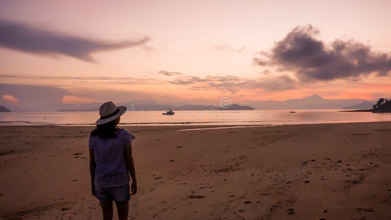 Aziatisch vrouwensilhouet bij zonsopgang oceaan roze en oranje hemel stock afbeelding