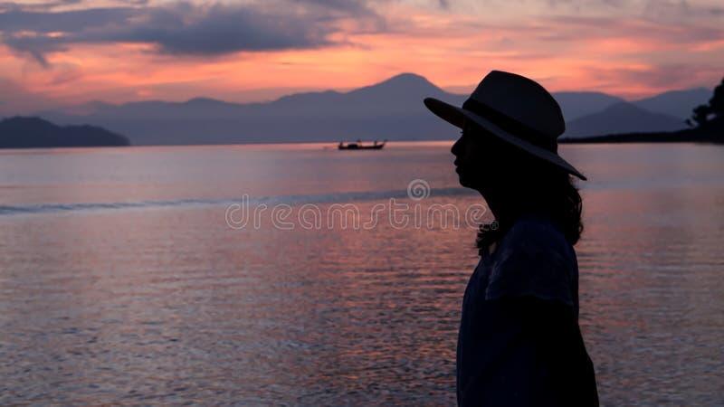 Aziatisch vrouwensilhouet bij zonsopgang oceaan roze en oranje hemel stock foto