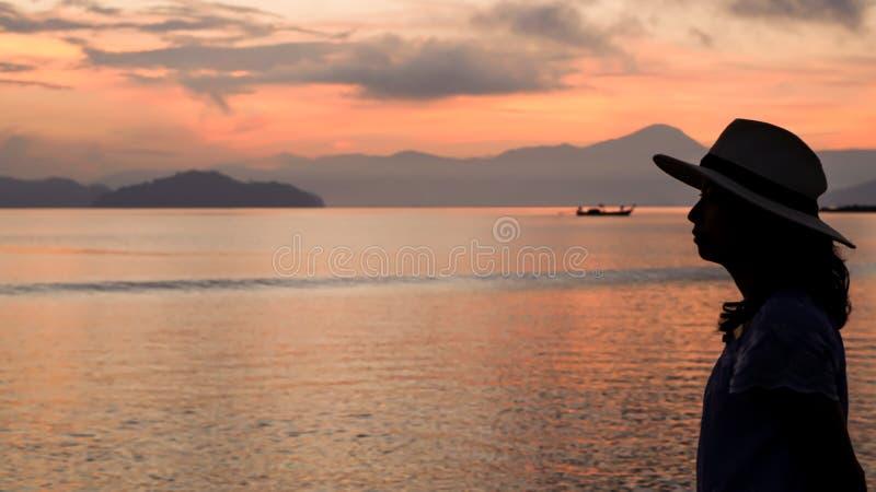 Aziatisch vrouwensilhouet bij zonsopgang oceaan roze en oranje hemel royalty-vrije stock afbeelding
